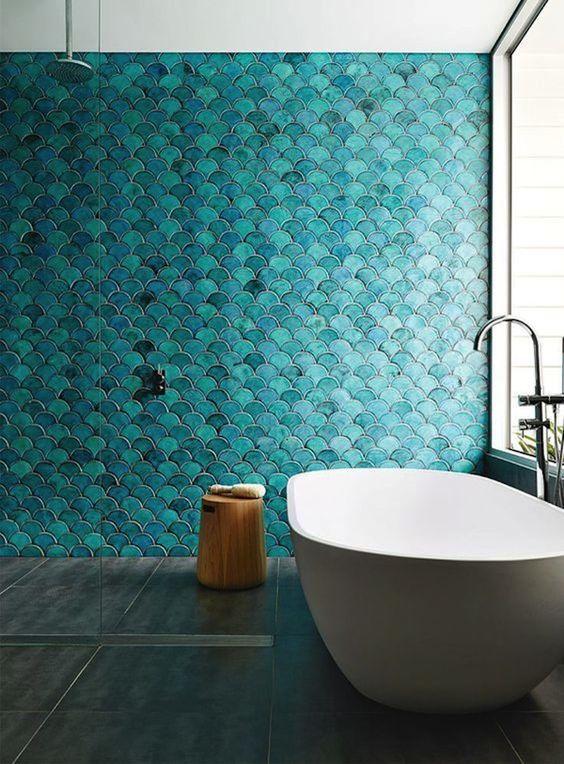 a turquoise fish scale tile statement wall makes the space feel mermaid-like, and a serene tub adds to it