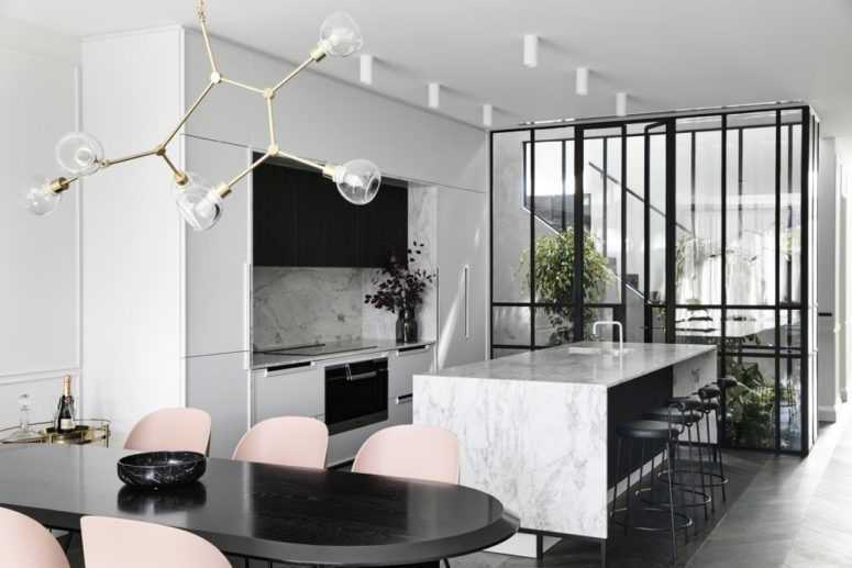 The kitchen is done in white and with white stone countertops and a backsplash, it flows into a dining space