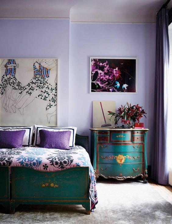 a bold bedroom with lilac walls, turquoise and emerald furniture and purple and pink details