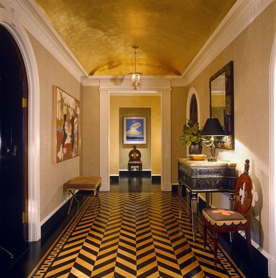 a bold mid century modern foyer with a metallic arched ceiling and a bold chevron floor