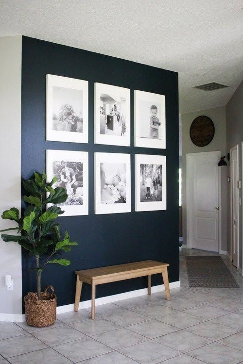 a statement navy wall with a gallery wall of black and white family photos