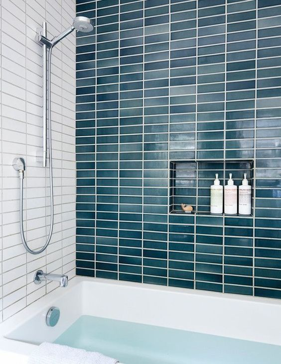 a statement teal long and narrow tile wall adds color to the bathroom making it feel seaside-like