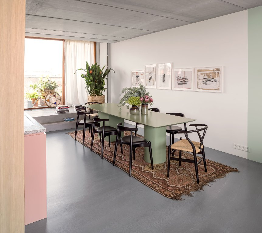 The dining room is done with black chairs and a pastel green table plus artworks