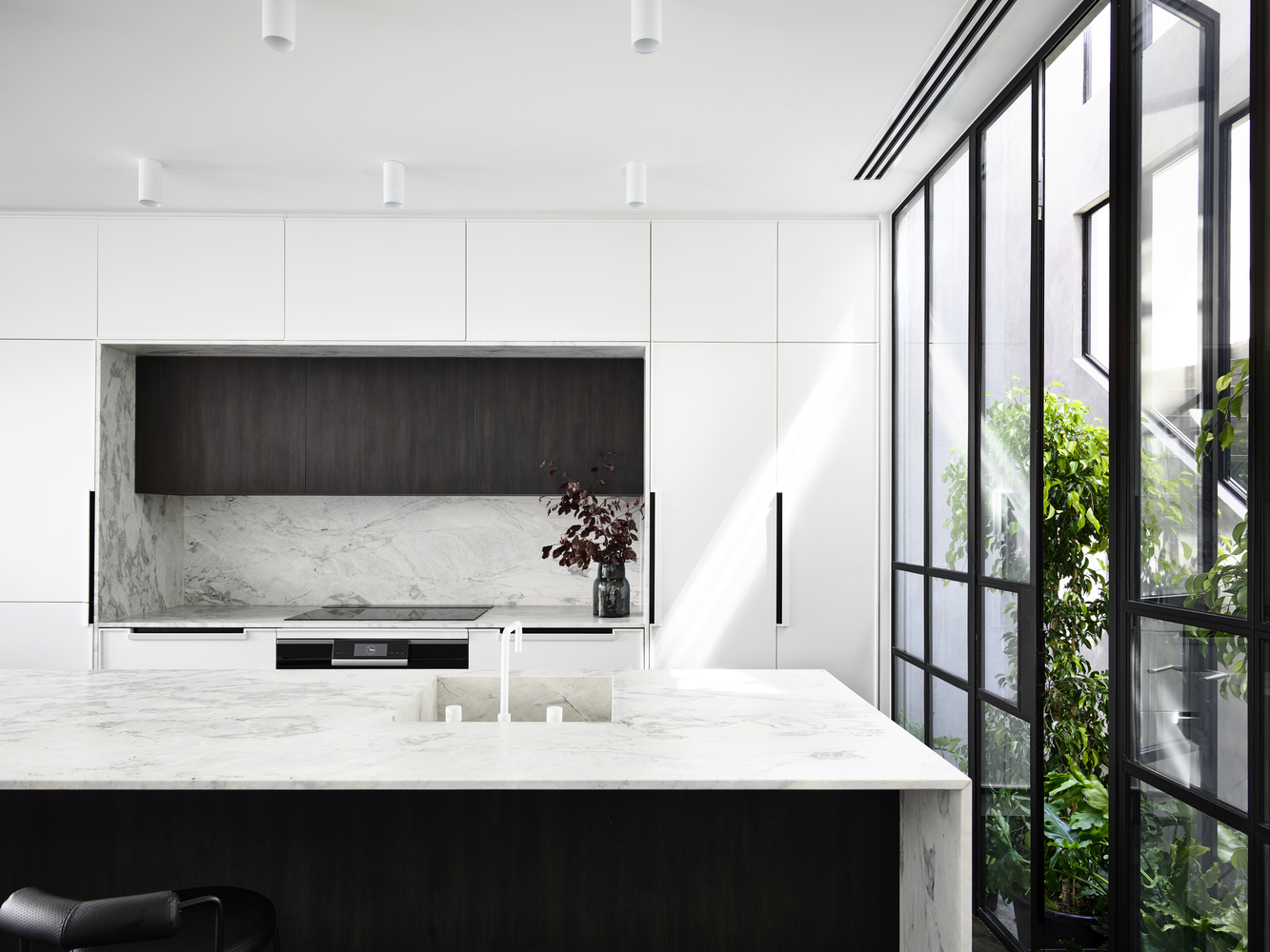 The kitchen is opened to the atrium with fresh greenery and light