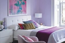 04 a bright bedroom with lilac walls, a pink chair and bright bedding and pillows is a great place to wake up