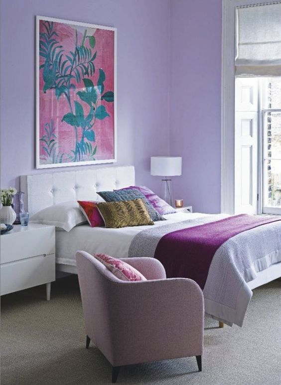 a bright bedroom with lilac walls, a pink chair and bright bedding and pillows is a great place to wake up