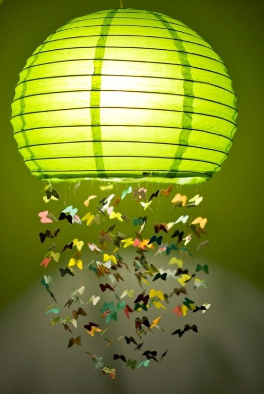 a colorful Regolit lampshade with some paper butterflies attached is a whimsical decoration