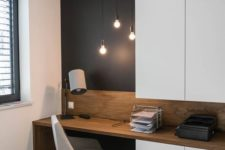 04 a home office nook is visually separated from the rest of the space with a black statement wall