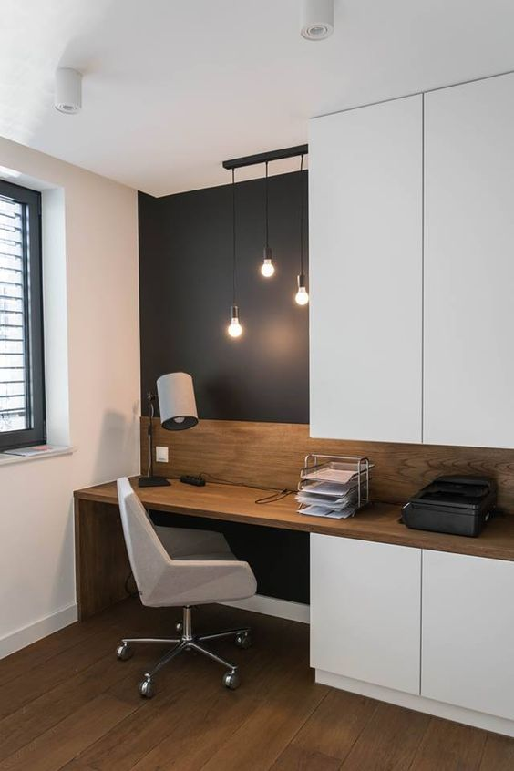 a home office nook is visually separated from the rest of the space with a black statement wall