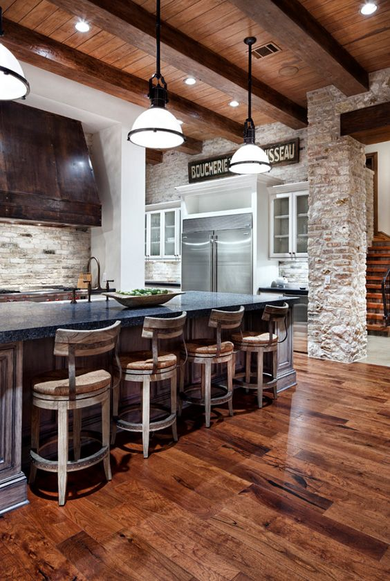 a rustic kitchen with a rich colored wood floor and whitewashed vintage wooden chairs
