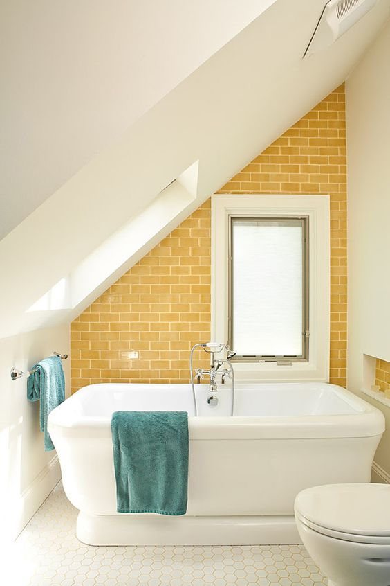 a small attic bathroom with a statement sunny yellow tile wall that makes it more welcoming