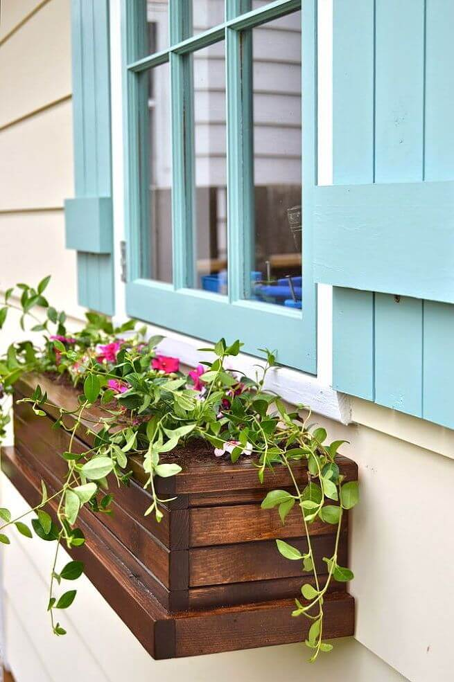 a stained slatted wood window box with fresh flowers adds interest to the light blue shutters