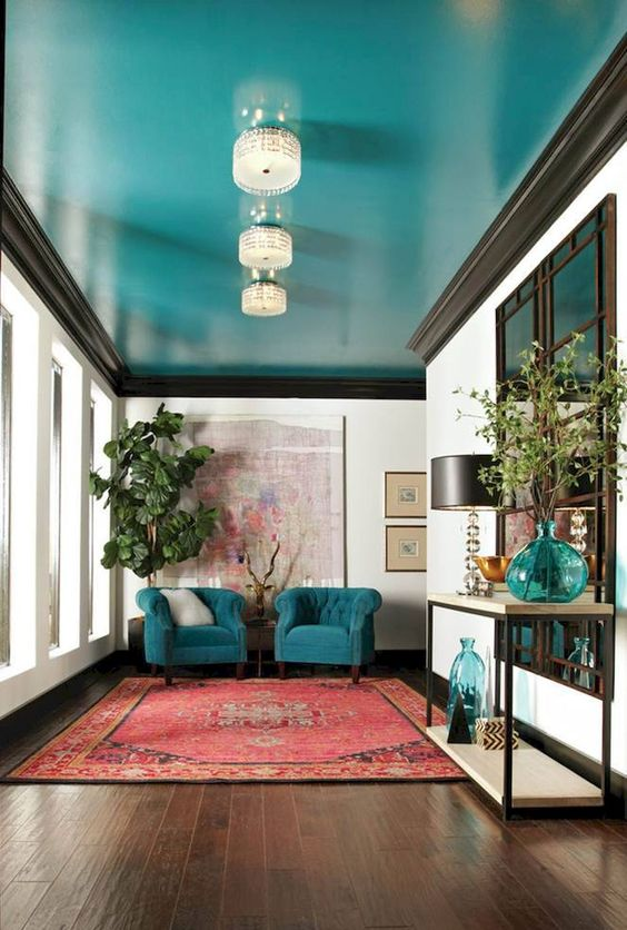a super bright turquoise ceiling and matching chairs and accessories are a great color statement in the space