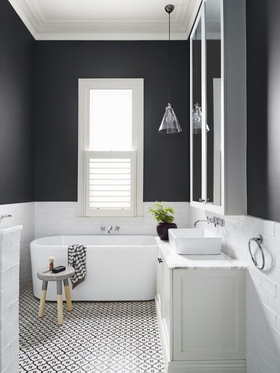 black walls clad with white tiles create a monochromatic yet catchy and contrasting look