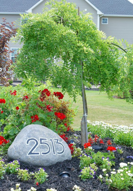 integrate your house numbers in landscaping placing them on a large rock on your lawn or in the front yard garden