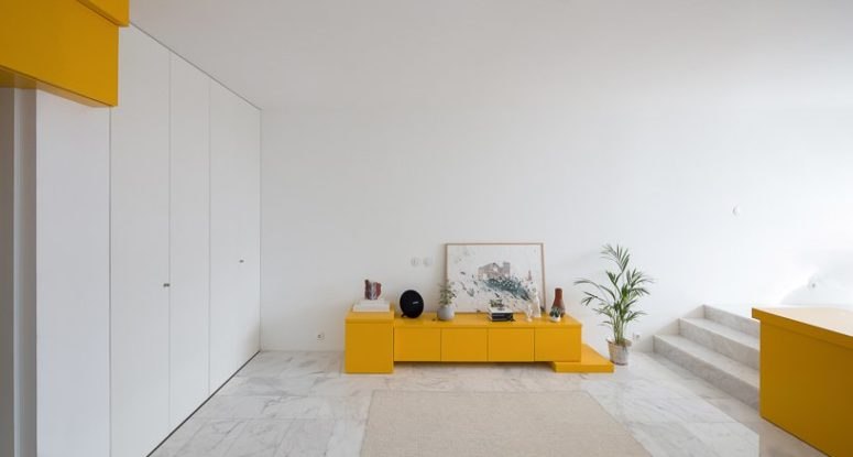 A small storage cabinet in bold yellow in the living room zone is also great for storage