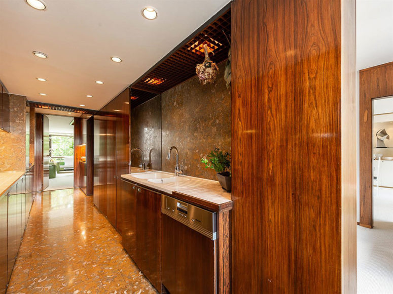 The kitchen is done with modern rich-colored wooden cabinets and stone surfaces here and there