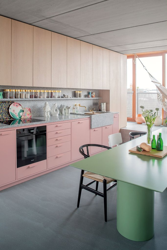 The kitchen is done with wooden and pink cabinets and a terrazzo countertop and backsplash