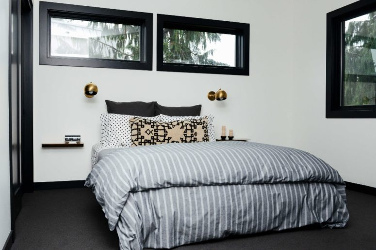 The master bedroom is done with touches of black for more drama and a bed with floating nightstands