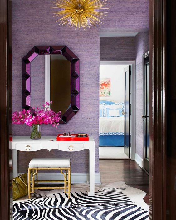 a bright entryway with lilac wallpaper walls and a purple mirror, gold touches add a glam feel to the space