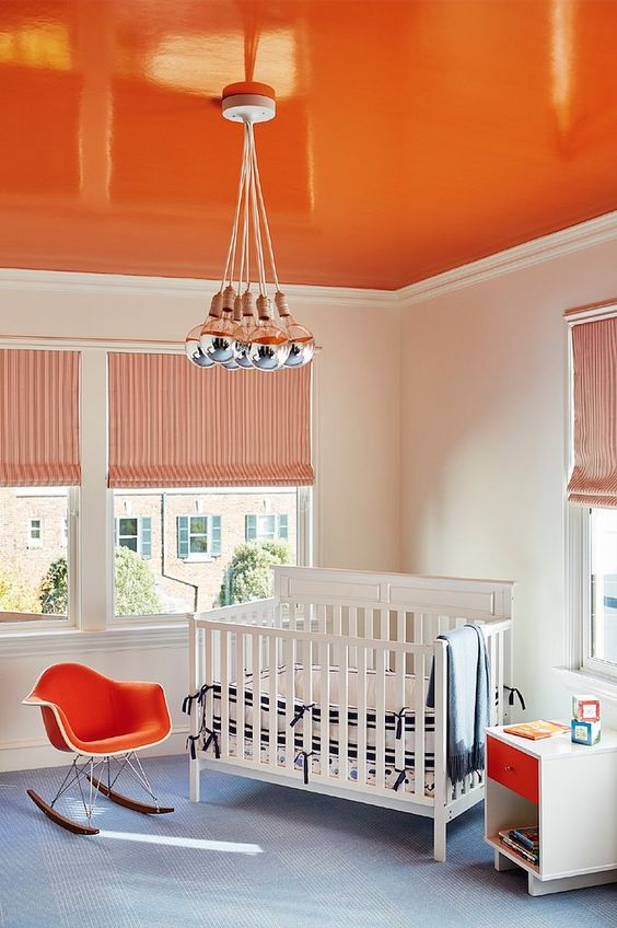 a bright orange ceiling, a matching chair and drawer to create a bold and welcoming kid's room