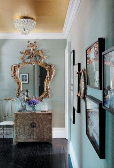 a chic aqua entryway done with a gold ceiling and a vintage frame mirror plus a unique vanity