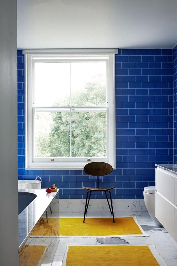 bold blue subway tiles on the wall make a statement and add an edge as subway tiles are a hot trend