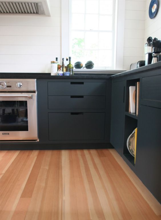 Douglas fir wood floor and graphite grey kitchen cabinets create a bold and chic modern look