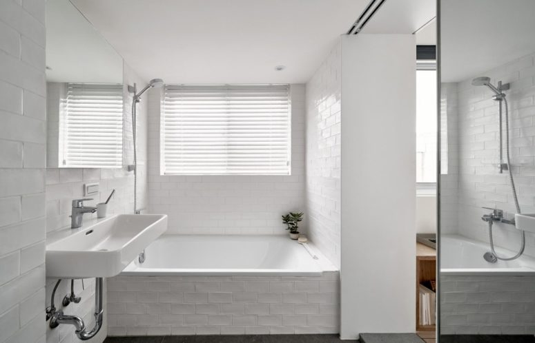 The bathroom is clad with white tiles, there's a covered window to have natural light yet privacy