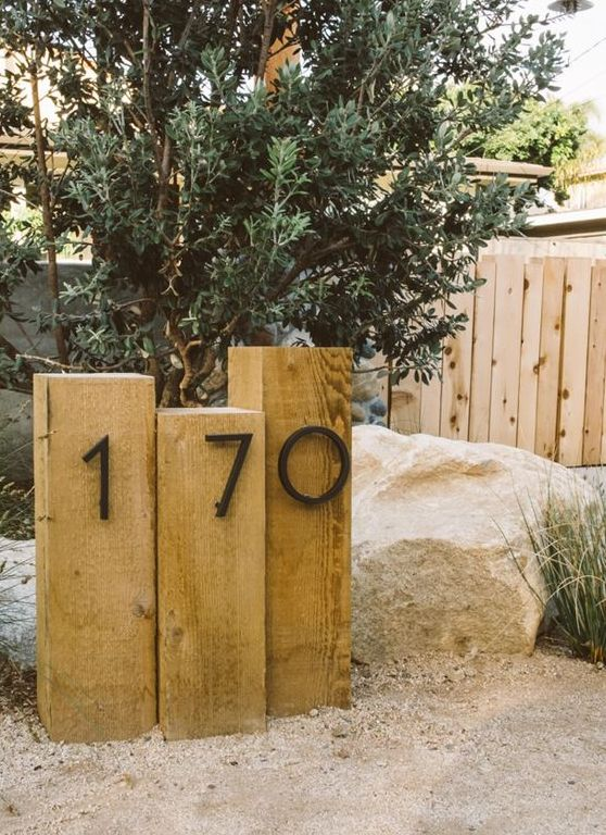 wooden posts with metal house numbers integrated right into the landscape is a stylish idea for a modern home
