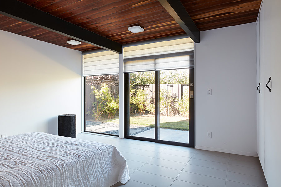 A partly glazed wall can be opened to outdoors and covered with Roman shades when the owners want some privacy