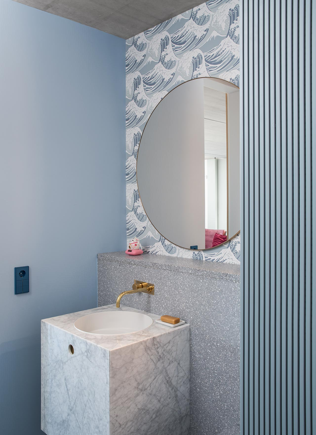 The bathroom features greys and blues, there's stone, terrazzo, wallpaper and paint to bring more textures in