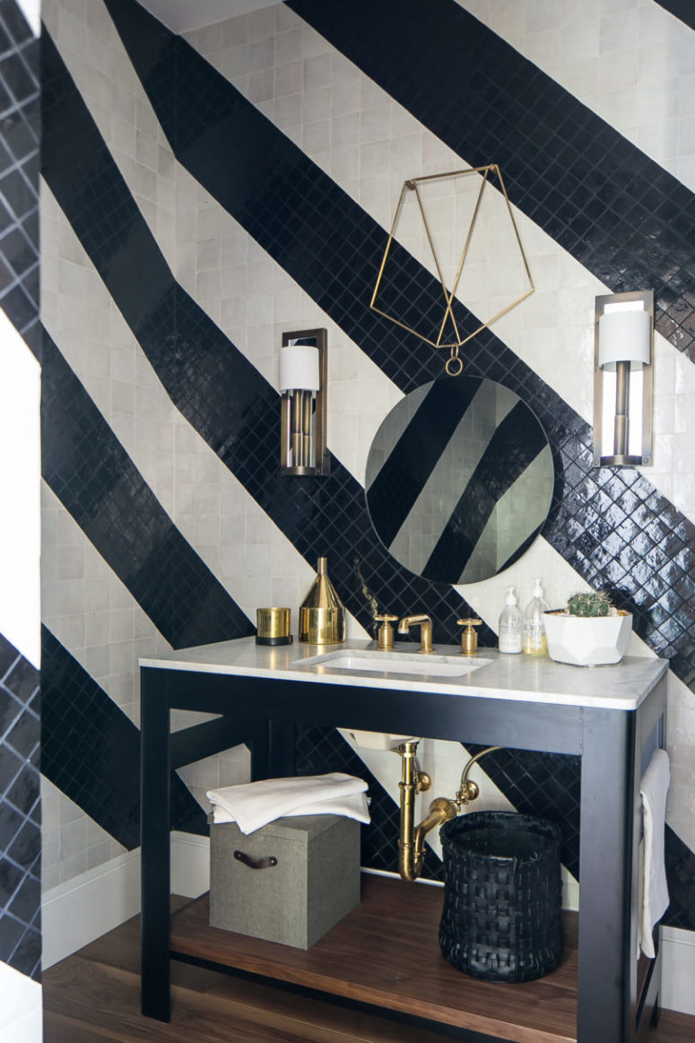 The bathroom is clad with black and white tiles done in stripes