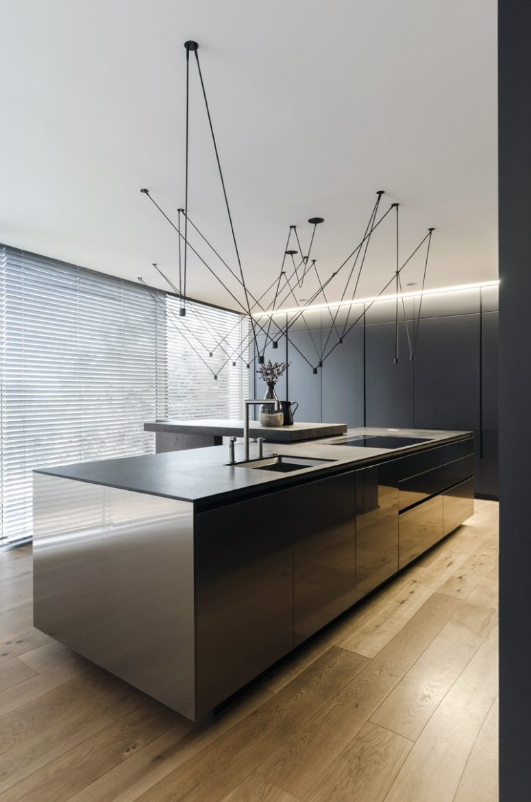 The kitchen is a dark and sleek one, with large cabinets and an oversized kitchen island with a breakfast space and suspended lamps