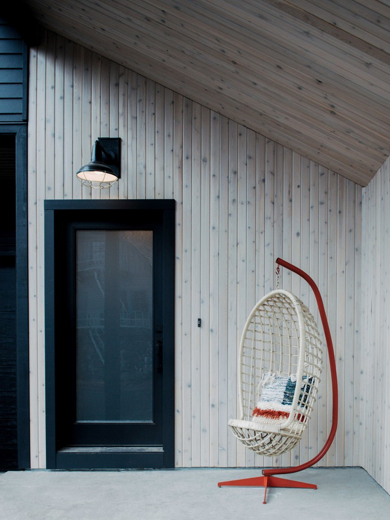 The porch is clad with light colored pine and there's a catchy pendant chair