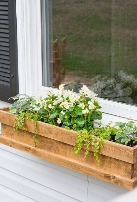 a cedar window box planter with much greenery and white flowers looks cute and rustic