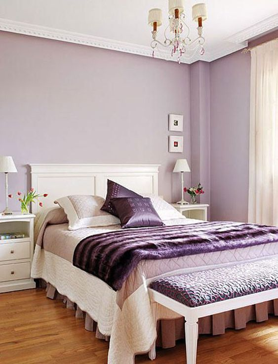 a feminine bedroom with lilac walls, purple accessories and an upholstered bench is a chic and refined idea