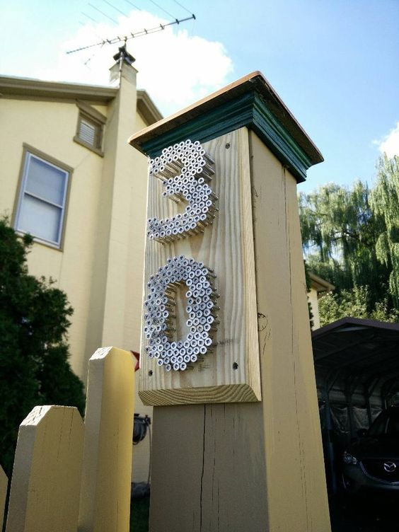 a post with metal nails that form house numbers is a stylish and bold idea with an industrial feel