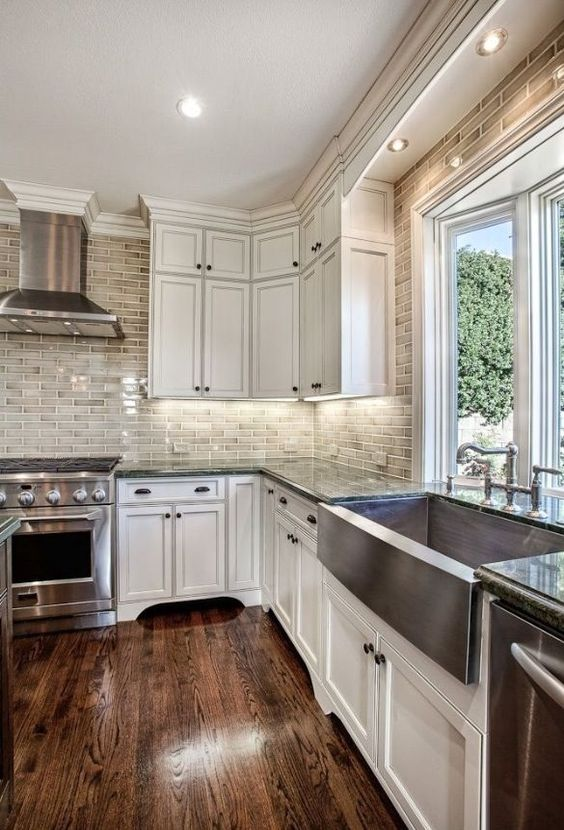 rich-colored hardwood floors and white wood cabinets are a chic and classic kitchen combo