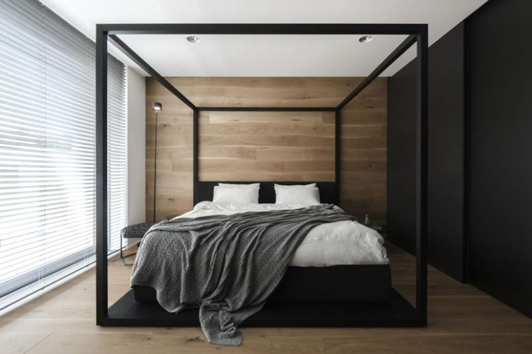 The master bedroom is done with wood, a black wall that conceals storage and a glazed wall covered with shades