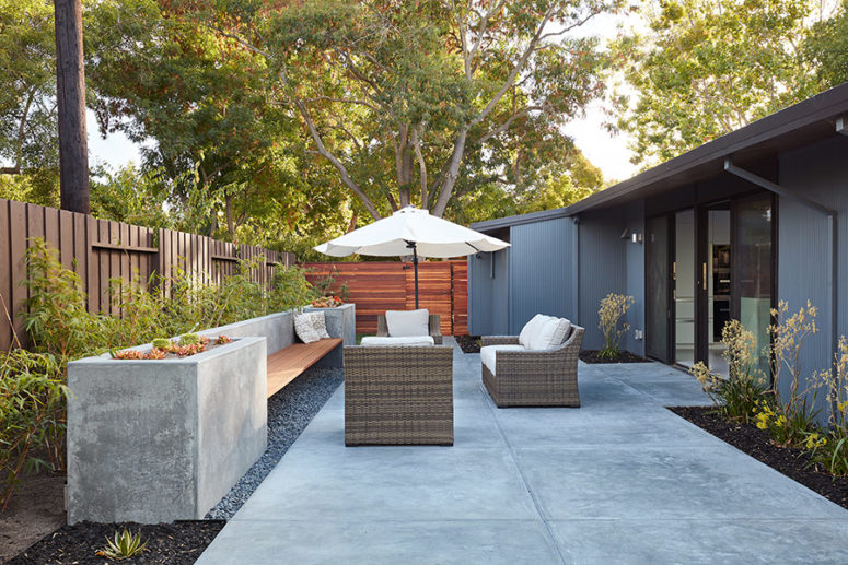 The outdoor space is done with wicker furniture, an umbrella and a concrete bench with built-in planters