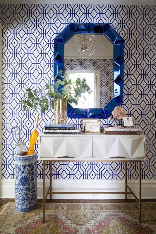 a bold blue printed wallpaper statement wall and a matching urn and mirror for a wow effect