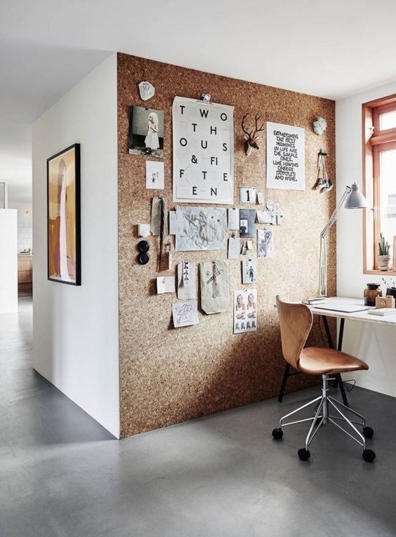 a home office nook spruced up with a cork statement wall, which can be also used for pinning notes