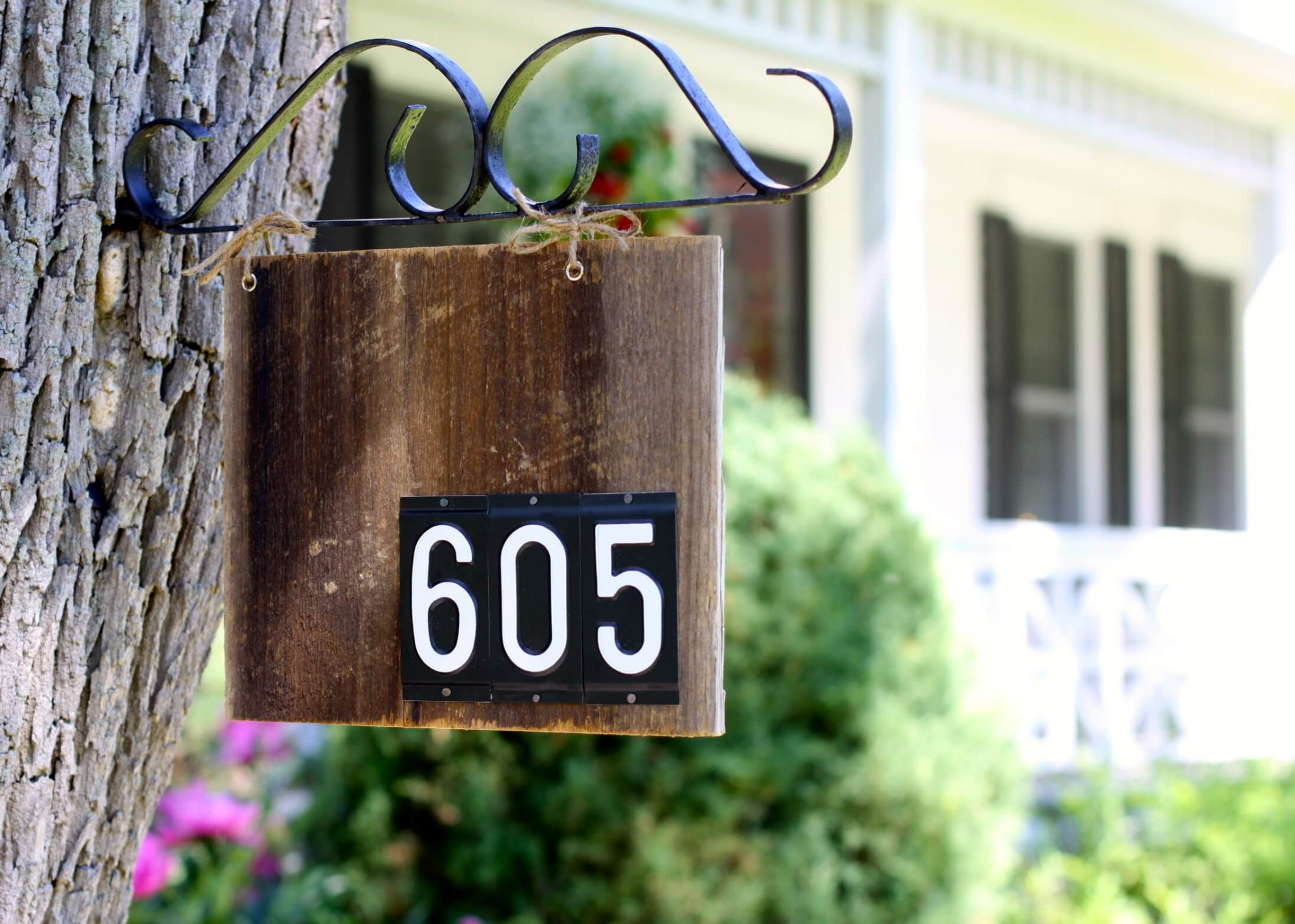 a house number sign hanging from a tree is a stylish vintage inspired idea for any home