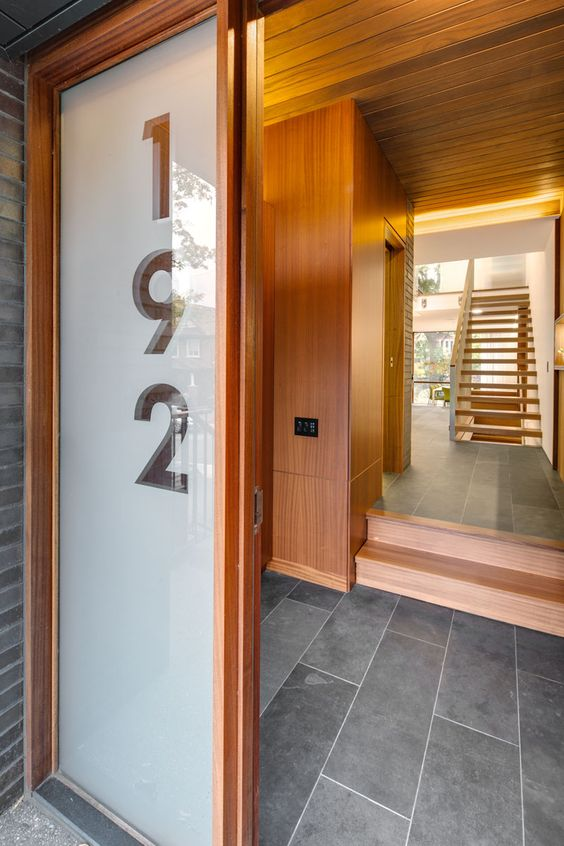 this front door, with an adjacent large glass panel showcasing the house number, guides visitors into the home