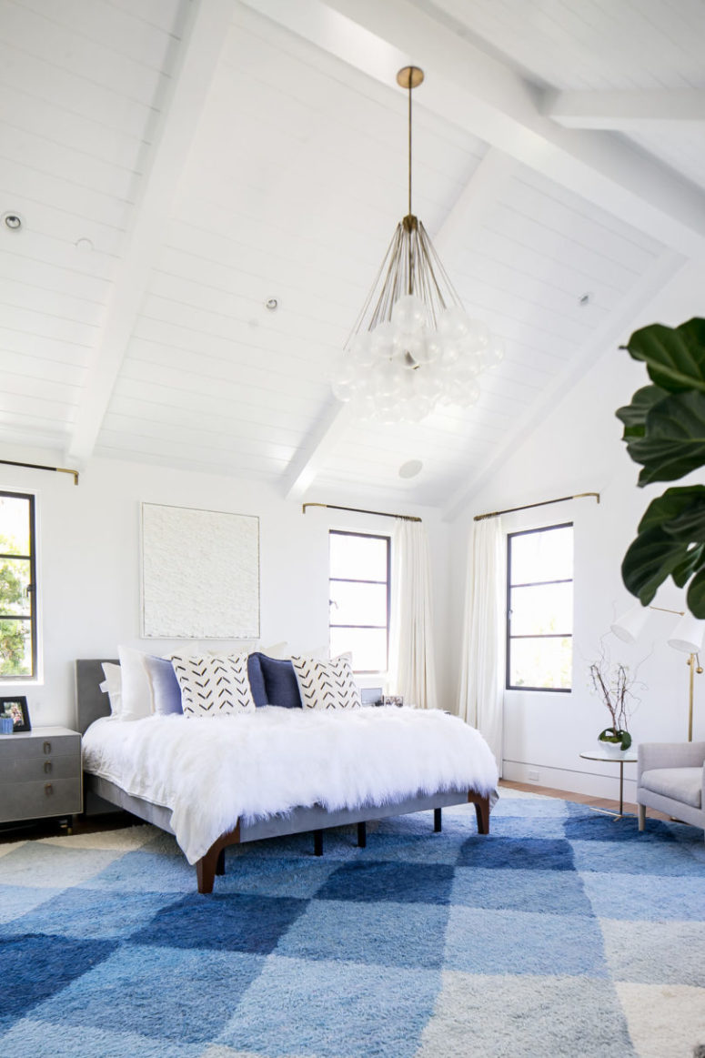 The master bedroom is very chic and cozy, done in blue and white with lots of texture done with textiles