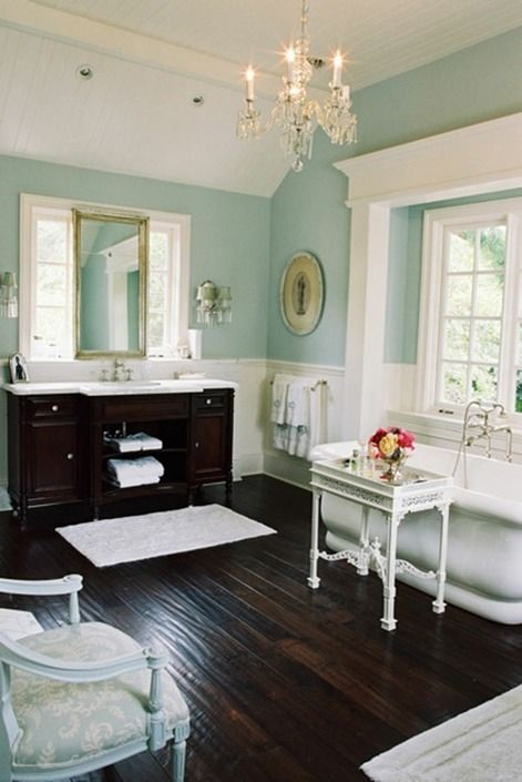 a dark stained floor and a matching vanity are of a dominant dark tone, and the rest of the furniture is whitewashed