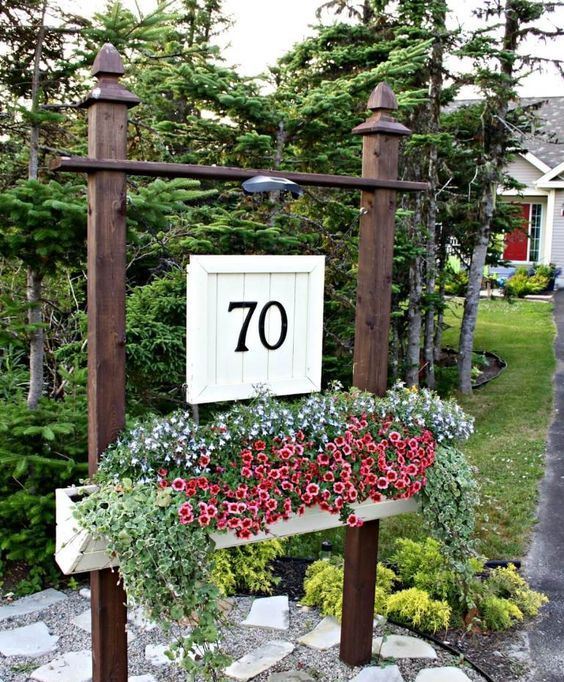 a large outdoor planter on stands with lush blooms and greenery and a wooden plaque with house numbers and an additional light