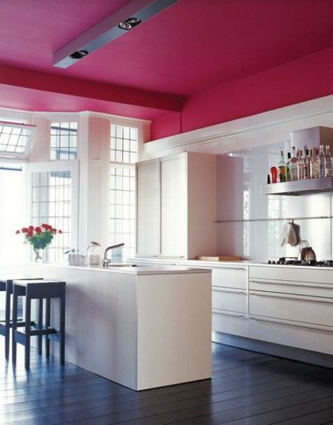 a neutral kitchen highlighted with a burgundy ceiling to visually separate it from the rest of the space