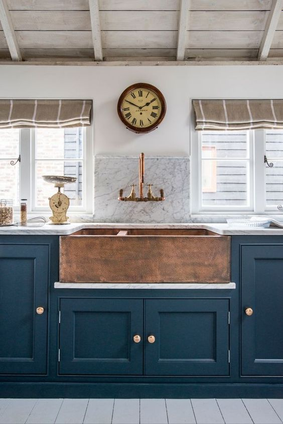 navy cabinets with brass knobs and a copper hammered sink for a vintage kitchen